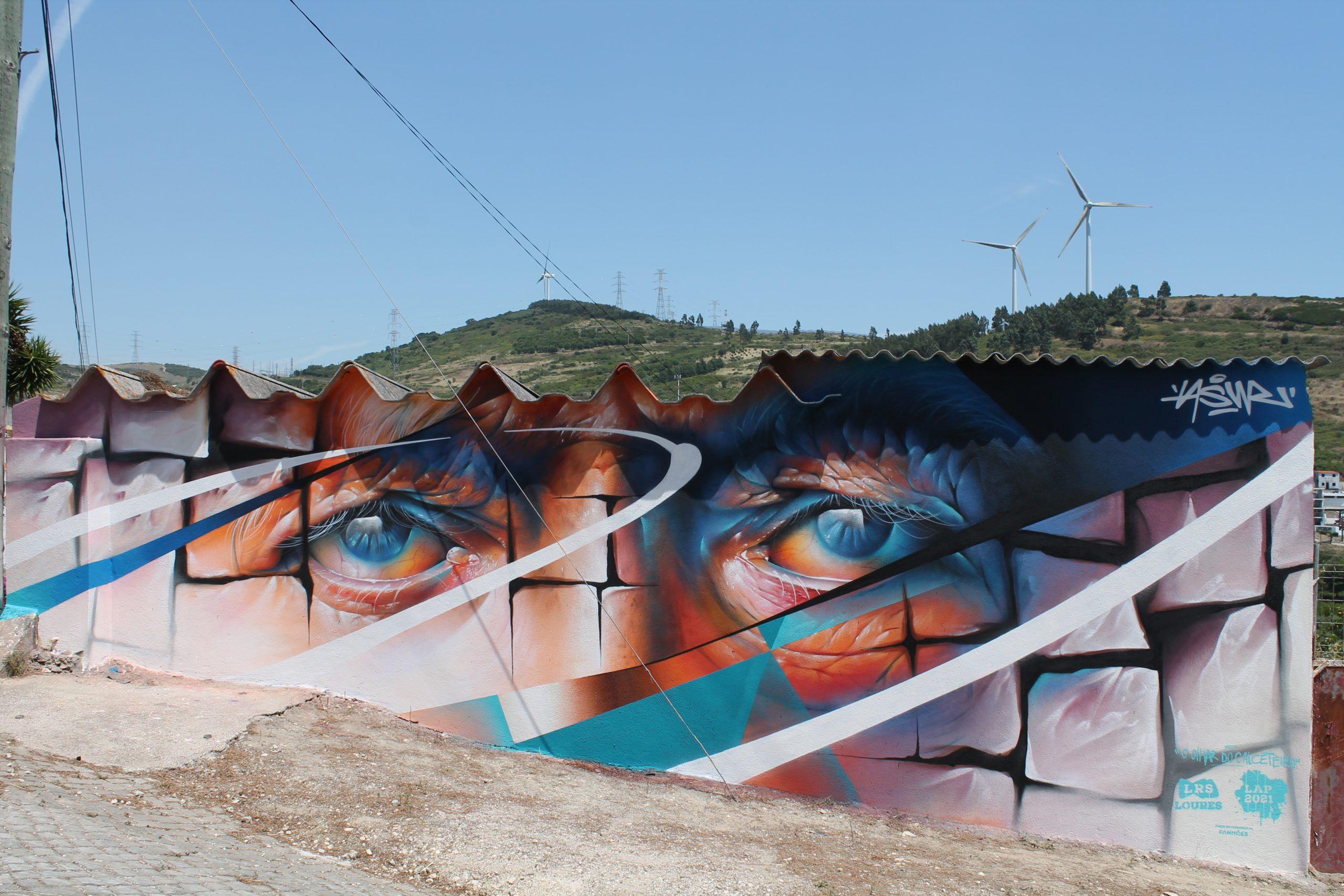 """Loures Arte Pública 2021 –Astreet art está de volta e a Freguesia de Fanhões recebeu o artista ASUR com a obra """" O Olhar do Calceteiro""""!"""